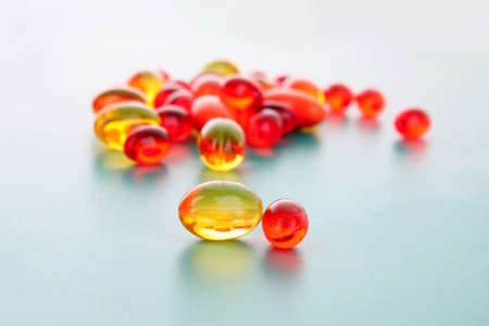 red and yellow  capsules of vitamins on a blue background photo