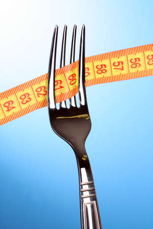 fork and measuring tape on blue background Stock Photo - 8721095