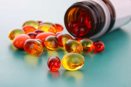 c vitamin: red and yellow  capsules of vitamins on a blue background Stock Photo