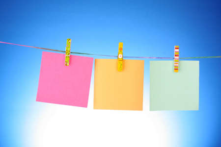 Blank paper sheets on a clothes line on a blue background Stock Photo - 8721748