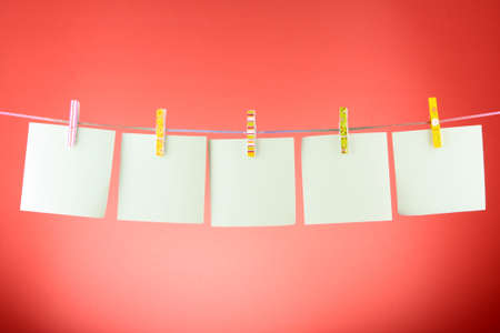 Blank paper sheets on a clothes line against the red background photo