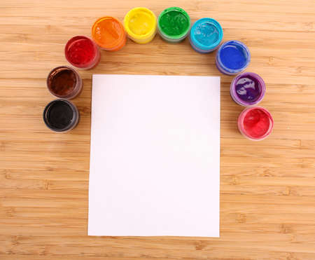 descriptive colour: Opened paint buckets colors and paper on the table