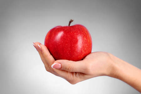 An apple on the hand on grey background photo