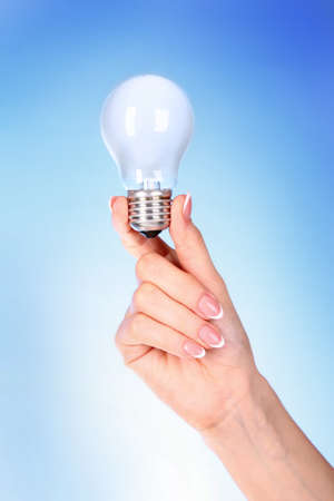hand with lightbulb on blue background Stock Photo - 8721790