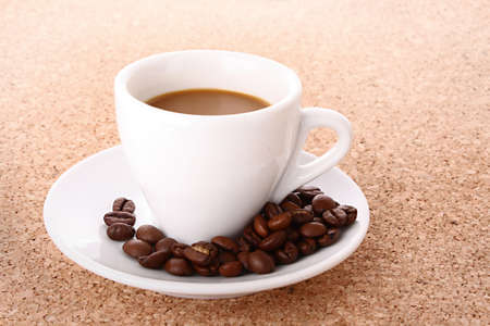 Small white  cup of coffee with coffee grain   on brown background photo