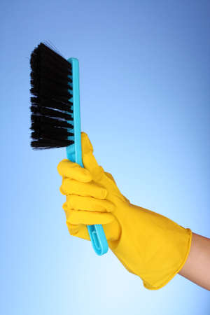 hand with dustpan and brush on blue photo