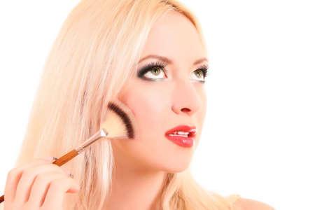 Young woman applying eye shadow, isolated on white photo