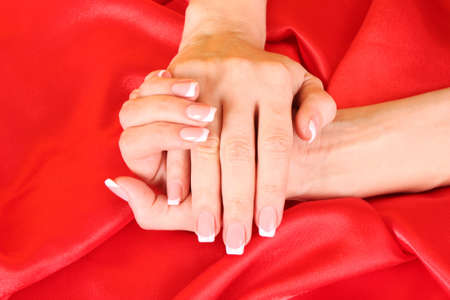 Beautiful woman hands with french manicure on red background photo
