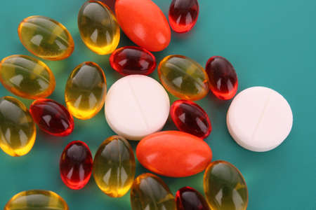prescribed: red and yellow  capsules of vitamins on a blue background Stock Photo
