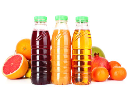bottles of juice  with ripe fruits on white background photo
