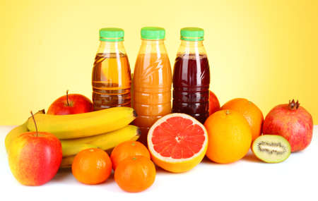 bottles of juice  with ripe fruits on yellow background photo