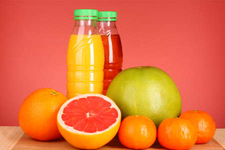 bottles of juice  with ripe fruits on yellow background Stock Photo - 8812995