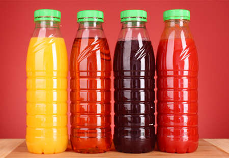 juice squeezer: bottles of juice on red  background