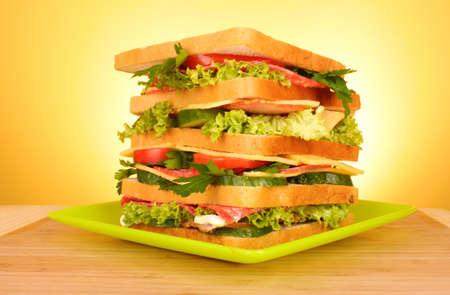 Huge sandwich on yellow background photo