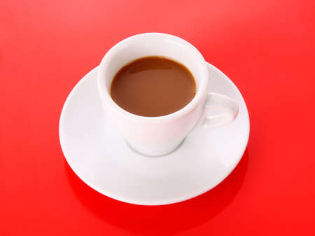 Small white cup with coffee on red background photo