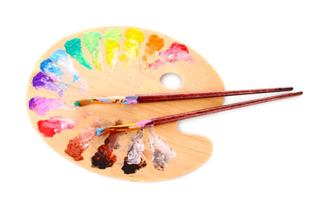 wooden art palette with blobs of paint and a brush on white background Stock Photo - 8911699