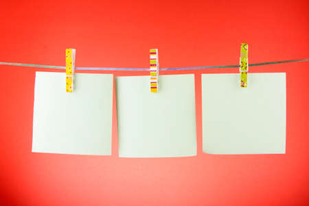 Blank paper sheets on a clothes line against the red background Stock Photo - 8983058