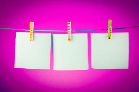 Blank paper sheets on a clothes line against the red background Stock Photo - 8983020
