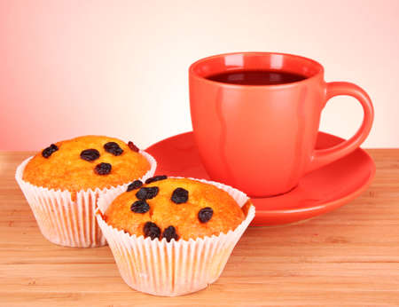 Muffins with raisins and red cup on wooden surface photo