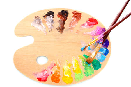 color palette: wooden art palette with blobs of paint and a brush on white background