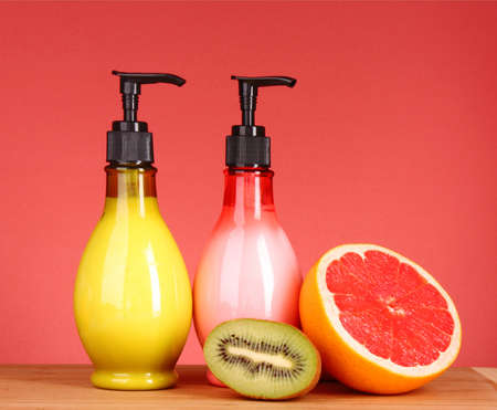 Fruity body lotion, grapefruit and kiwi fruit on a red background photo