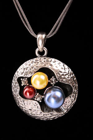 Golden pendent with pearls  on black photo