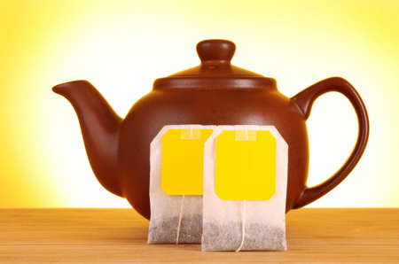 Close-up of tea bag and teapot on yellow background