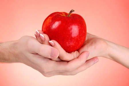 Apple between man and woman hand on red background photo