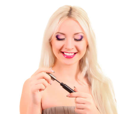 portrait of a young pretty blonde  woman applying mascara photo