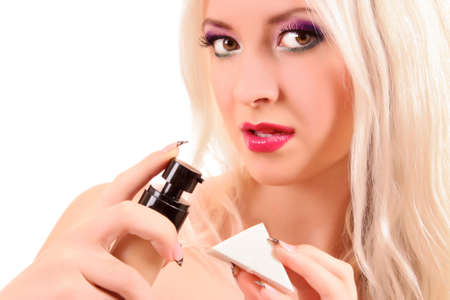beautiful  young blonde  woman applying face foundation photo