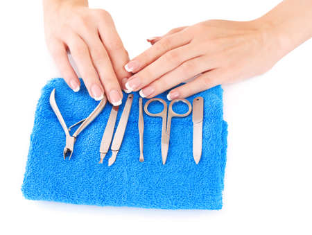 Womans hands and manicure instruments on blue  background photo