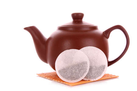 Close-up of tea bag and teapot isolated on white background photo
