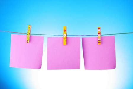 Blank paper sheets on a clothes line on a blue background Stock Photo - 9211507