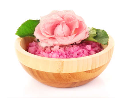 bowl of pink bath salt with flower on white photo