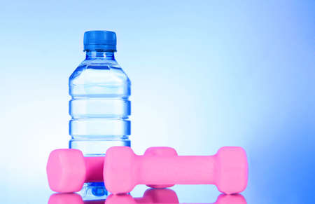 dumbbells and bottle of fresh water on blue photo