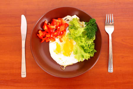 Frying egg with fork and knife on the table photo