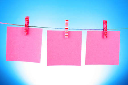 Blank paper sheets on a clothes line on a blue background Stock Photo - 9211189