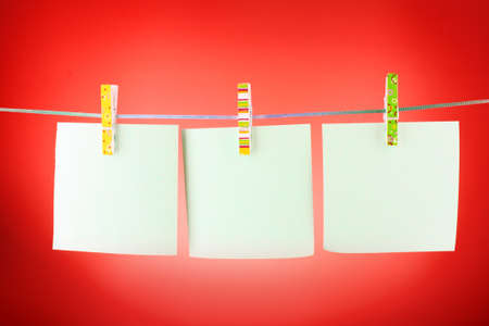 Blank paper sheets on a clothes line against the red background Stock Photo - 9251107