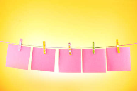 Blank paper sheets on a clothes line against the yellow background photo