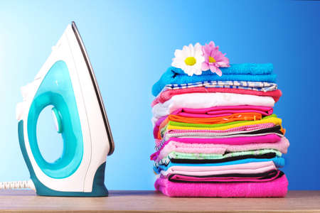 Pile of colorful clothes and electric iron  on blue background photo