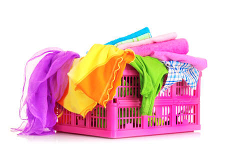 Bright clothes in a laundry basket on white background photo