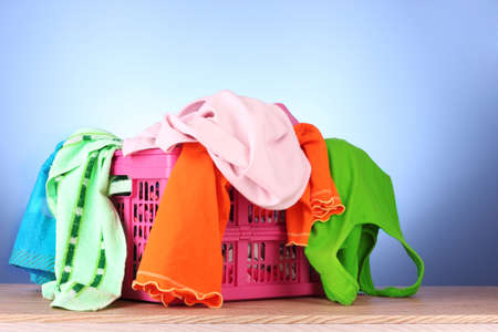 Bright clothes in a laundry basket on blue background Stock Photo - 9251234