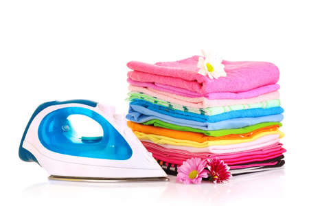 electric material: Pile of colorful clothes and electric iron  over white background