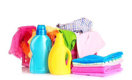 Bright clothes in a laundry basket and liquid laundry detergent  on white background photo