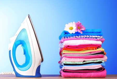 umyty: Pala kolorowe ubrania i elektryczne żelaza na niebieskim tle