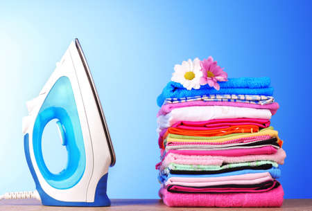 white washed: Pile of colorful clothes and electric iron  on blue background Stock Photo
