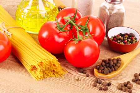 Pasta spaghetti with tomatoes, olive oil, peper  and basil on a wooden background Stock Photo - 9371130