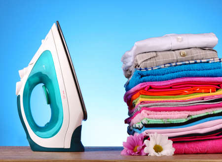 Pile of colorful clothes and electric iron  on blue background Stock Photo - 9473662
