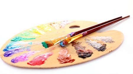 paleta de pintor: paleta de madera de arte con manchas de pintura y un pincel sobre fondo blanco Foto de archivo