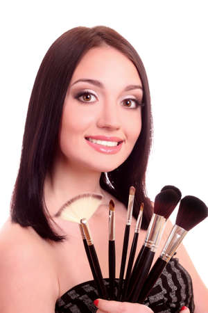 Beautiful young woman with make-up brushes near attractive face Stock Photo - 9579454